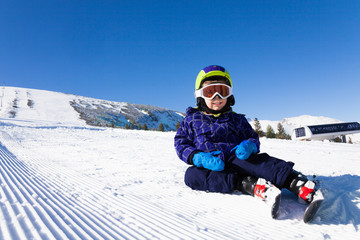 Small boy in ski mask sitting on the snow