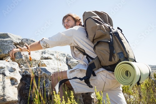 canvas print picture Handsome hiker hiking through rough terrain