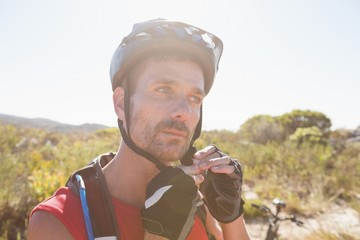 Fit cyclist adjusting helmet strap on country terrain