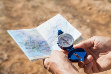 Hiker holding his compass and map in the countryside