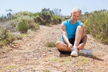 Smiling jogger tying his shoelace on mountain trail