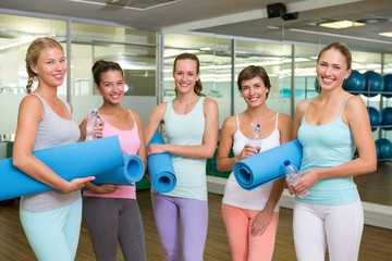 Smiling women in fitness studio before yoga class