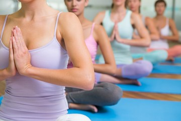 Yoga class in lotus pose in fitness studio