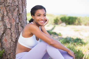 Fit woman sitting against tree smiling