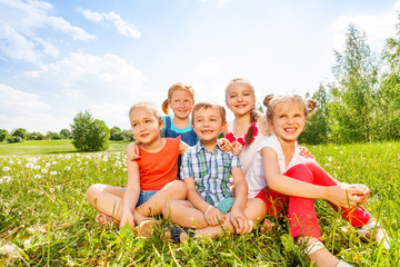 Five kids smile sitting on a grass