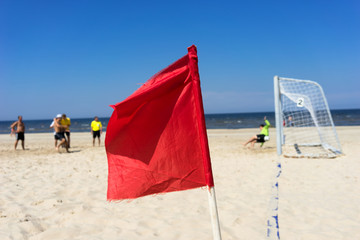 People play football on the beach on a background of red flag