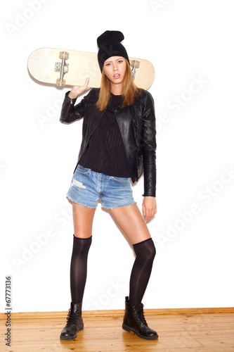 Trendy girl  in black jacket and beanie with skateboard