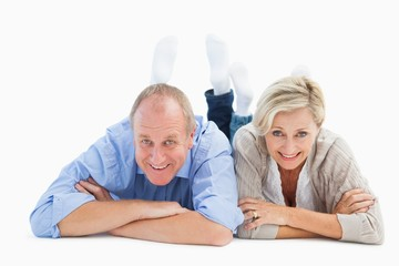 Happy mature couple lying and smiling