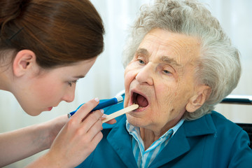 Doctor examines elderly woman for sore throat