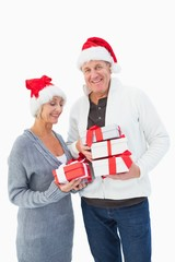 Festive mature couple in winter clothes holding gifts