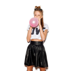 Young woman blowing a pink balloon