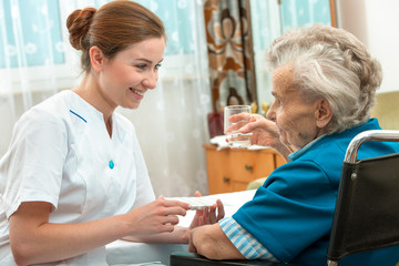 female nurse giving senior woman medical pills