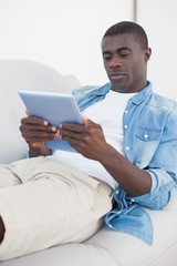 Casual man lying on sofa using his tablet pc