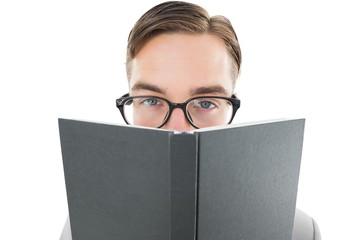 Geeky man looking over book