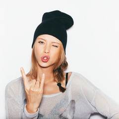 Young beautiful woman winking and giving the Rock and Roll sign