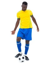 Football player in yellow kicking ball