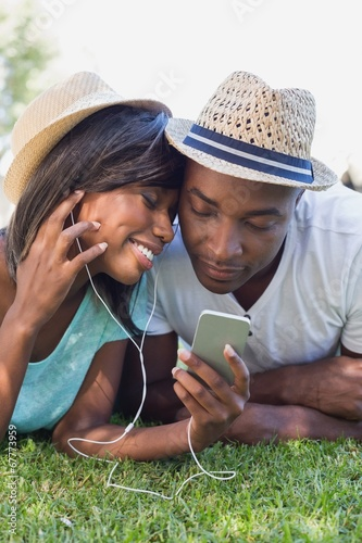 Happy couple lying in garden together listening to music