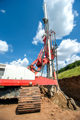 Industrial drilling rig at construction site making holes