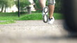 Joggers legs jogging on track in park, super slow motion