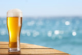 Fototapety Beer glass on a blurred background of the sea.