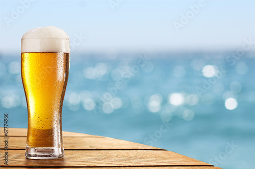 Beer glass on a blurred background of the sea. - 67774966