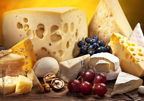 Different types of cheese over old wooden table. - 67775701