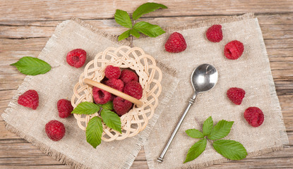 Top view of small basket with fresh raspberries with leaves