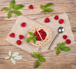 View from above of wicker basket with raspberries
