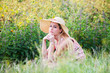 serious portrait of young woman in field wearing straw hat