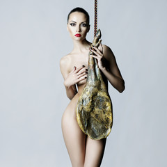 Nude elegant woman with Iberian jamon