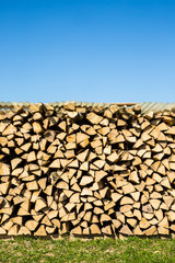 Pile of chopped firewood with green grass and blue sky