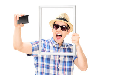 Man holding a picture frame and taking selfie