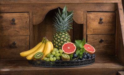 fruits (pineapple, banana, grapes, kiwi, grapefruit) on a dish