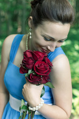 smiling girl with bouquet of red roses