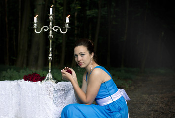 girl keeps rose and sits near a table with a silver candlestick