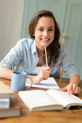 Student teenage girl studying at home smiling
