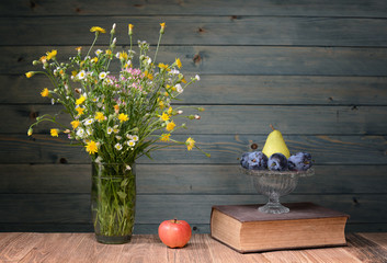 Flowers in a vase made ​​of glass, books and fruit