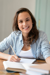 Teenage student girl studying at home smiling