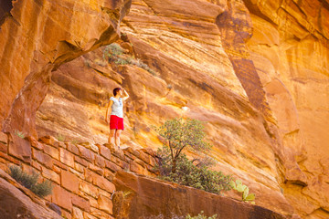 Tourist among red rocks in Zion National Park