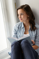 Teenage girl sitting with book by window