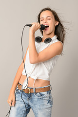 Singing teenage girl with microphone closed eyes
