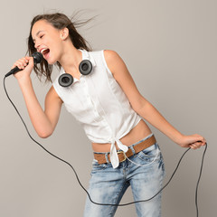 Singing teenage girl with microphone karaoke music