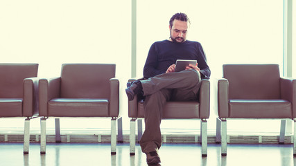 Man using digital tablet pc at an airport lounge, waiting room.