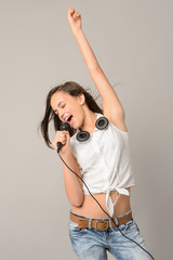 Teenage girl dancing singing with microphone