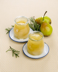 Canned pear compote in jar with rosemary