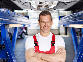 Car mechanic under a car in a garage