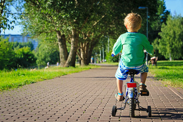 little boy riding bike in the park