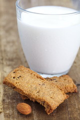 Almonds cookies and cup of milk on wood background