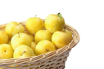 Yellow plums in wicker basket