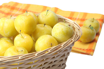 Yellow plums in wicker basket